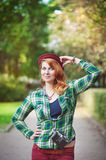 Cheerful hipster redhead girl in hat with retro camera Stock Image