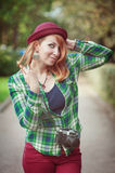 Cheerful hipster redhead girl in hat with retro camera Stock Images