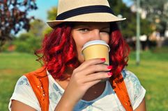 Cheerful hipster woman with red curly hair drinking morning coffee in sunshine light. stock image