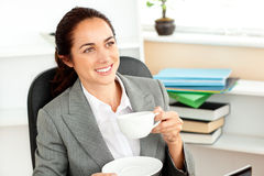 Cheerful hispanic businesswoman drinking coffee Royalty Free Stock Images