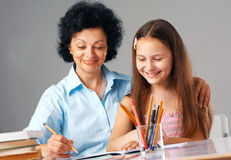 Cheerful Homework. Grandmother helping her granddaughter with her home-work Royalty Free Stock Photos