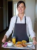 Cheerful hotel maid serving breakfast Stock Photos