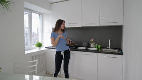 Cheerful housekeeper dancing and sings with pan and plates in hands while cooking meal at kitchen at home in vacation stock video