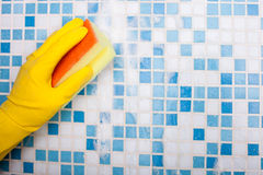 Cheerful houseman is doing clean-up in bathroom Royalty Free Stock Images