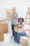 Cheerful housemates carrying cardboard moving boxes. And smiling at camera in new home Stock Photos