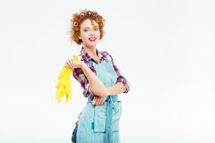 Cheerful housewife in blue apron holding yellow rubber gloves Royalty Free Stock Photo