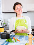 Cheerful housewife cooking rice in pan Stock Image
