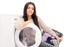 Cheerful housewife holding a laundry basket Stock Photos