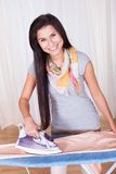 Cheerful housewife ironing the clothes Stock Photos