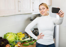 Cheerful housewife making photo of herself Royalty Free Stock Image