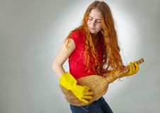 Cheerful housewife playing on her guitar broom. The maid plays on the broom as if she has a guitar in her hands Stock Photography