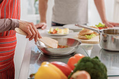Cheerful housewife preparing dinner for husband royalty free stock photo