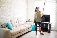 Happy woman feeling good after cleaning living room. Cheerful housewife standing with cleaning equipments in living room Stock Photos