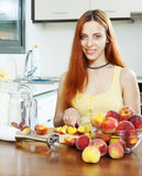Cheerful houswife cooking with peaches Stock Images
