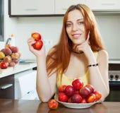Cheerful houswife holding nectarines at  kitchen Royalty Free Stock Image