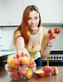 Cheerful houswife taking peaches Stock Images