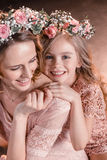 Cheerful hugging daughter and mother in flowers wreathes. Portrait of cheerful hugging daughter and mother in flowers wreathes Royalty Free Stock Images