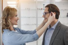 Cheerful husband and wife in optician shop royalty free stock photos