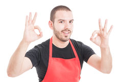 Cheerful hypermarket clerk showing double ok sign Royalty Free Stock Photography