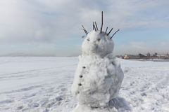 The cheerful incomplete snowman standing against the sky in the Royalty Free Stock Photography