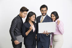 Cheerful Indian business people team happily looking at the laptop. On white background Royalty Free Stock Photography