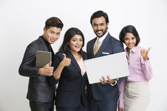 Cheerful Indian business people team happily posing with laptop. On white background Stock Image