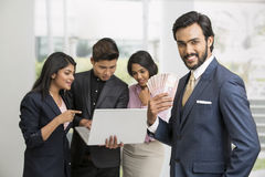 Cheerful Indian businessman holding rupees with his busy colleagues Stock Photo