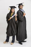 Cheerful Indian college graduates wearing cap and gown holding diploma Stock Photo