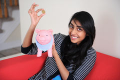 Cheerful Indian girl holding coin and piggybank Stock Photography