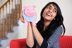 Cheerful Indian girl holding her Piggybank Stock Photos