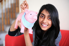 Cheerful Indian girl holding piggybank Stock Images