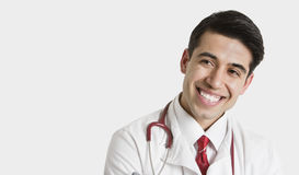 Cheerful Indian male doctor looking sideways over light gray background Stock Photography