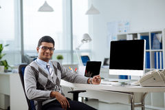 Cheerful Indian manager. Portrait of cheerful Indian manager at his table looking at the camera Royalty Free Stock Photos