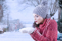 Cheerful indian woman blowing snow on her palm Stock Photo
