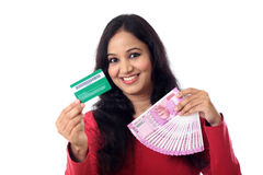 Cheerful Indian woman holding a bunch of Indian rupee and credit Stock Photos