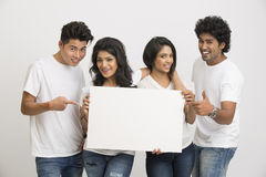 Cheerful Indian young people holding blank white board Stock Photo