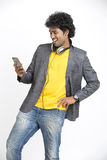 Cheerful Indian young urban man posing with mobile and headphone Royalty Free Stock Photos
