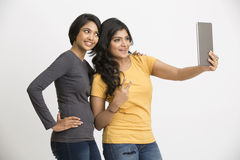 Cheerful Indian young woman using digital tablet. Beautiful Smiling young women using digital tablet on white Stock Image