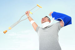 Cheerful injured young man hold up the crutch. Portrait of cheerful injured young man hold up the crutch Stock Photography