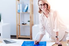 Cheerful intelligent woman leaning on the table. My workplace. Cheerful intelligent nice woman smiling and looking at you while leaning on her table Stock Photo
