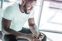 Cheerful international male person using his gadget. Checking email. Attractive young man keeping smile on his face and leaning elbows on knees while chatting royalty free stock image