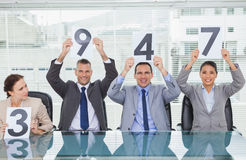Cheerful interview panel holding signs giving marks Stock Photo