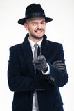 Cheerful investigator in coat, hat and gloves pointing on you. Cheerful handsome investigator in black coat, hat and gloves pointing on you over white background stock images