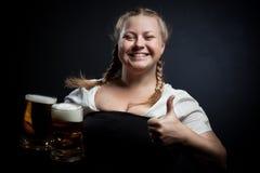 Cheerful Irish girl. With beer over dark background Royalty Free Stock Image