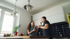 Young joyful couple have fun dancing and singing while having breakfast in the kitchen at home on holidays. Cheerful joyful couple have fun dancing and singing stock video footage