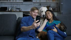 Multi ethnic family with pet dog posing for selfie