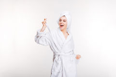 Cheerful joyful young woman in bathrobe with towel on head. Cheerful joyful young woman in bathrobe with towel on her head standing over white background Royalty Free Stock Images