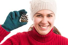 Cheerful and joyful young woman holding a pine cone. Wearing warm hat and gloves as winter holidays concept Stock Image