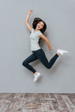 Cheerful joyful young woman jumping and having fun. Over grey background Stock Photography