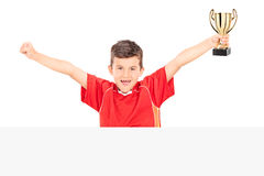 Cheerful junior holding a trophy behind a panel Stock Photo